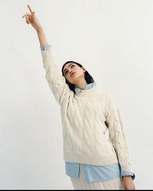 Mujer con chaleco blanco y camisa celeste