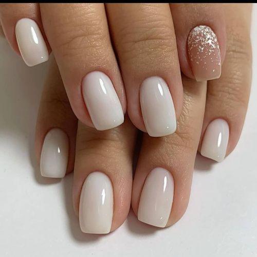 Uñas blancas con una uña color carne y con purpurina