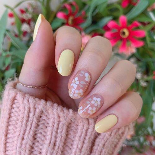 Uñas en amarillo y lila con flores blancas