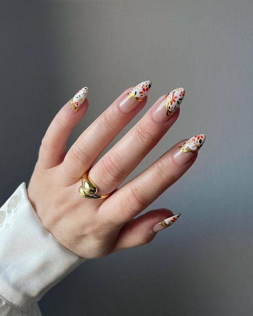 Uñas con media luna blanca, flores y anillo dorado