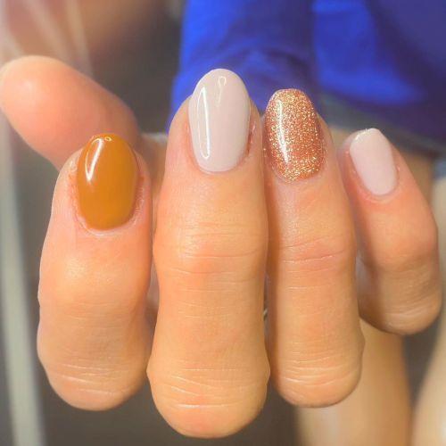 Uñas combinadas en dorado, blanco y ocre