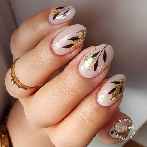 Uñas doradas cortas con glitter y hojas
