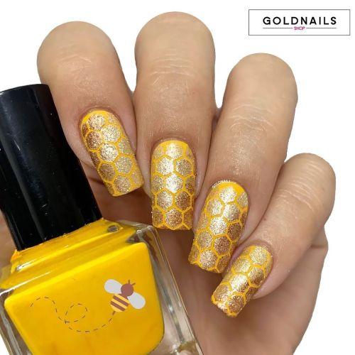 Uñas doradas con amarillo y figuras de polígonos