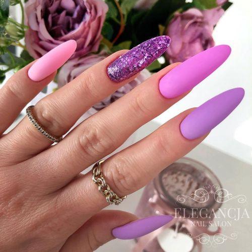 Uñas largas en distintos tonos lilas y con brillo