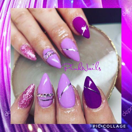 Uñas largas y en punta con lilas y morados y detalles en dorado y plateado