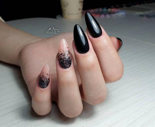 Uñas en negro con uñas en tonos carne y salpicada de negro