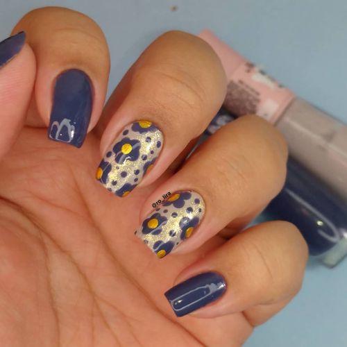 Uñas en azul eléctrico con flores y pintas amarillas