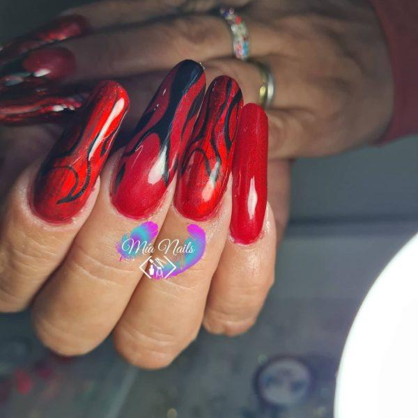 Uñas rojas largas en punta con dibujos negros