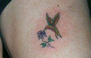 Tatuaje de colibrí y flor