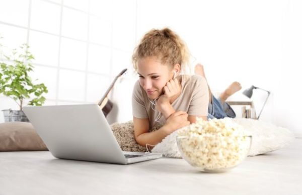 planes-para-hacer-en-casa-cuarentena-coronavirus-chica-mirando-ordenador-y-palomitas-istock