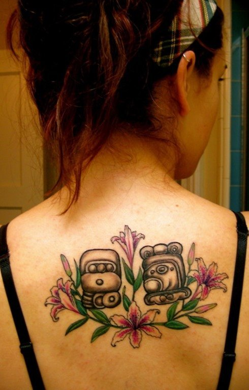 Two-Mayan-symbol-tattoos-surrounded-by-tattoos-of-lily-flowers