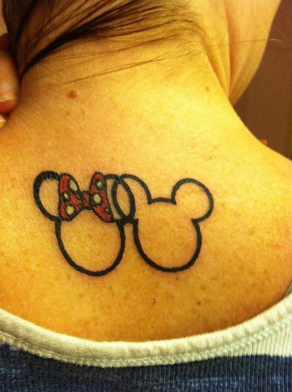 En este caso un bonito tatuaje doble con el símbolo de Mickey Mouse, la cabeza redonda y sus dos orejas, sin relleno en la parte central. Una de las orejas de Mickey y otra de Minnie se unen formando una intersección,no falta el gran lazo rojo a lunares de Minnie.